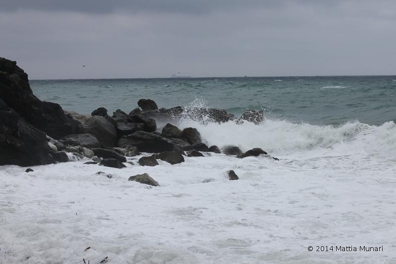 Schiuma che accompagna la risacca mare impetuoso